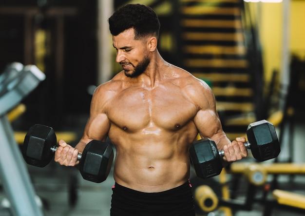 Strong man raising metallic dumbbells in a gym