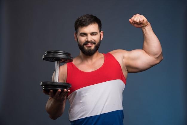 Сильный мужчина показывает мышцы и держит гантель.