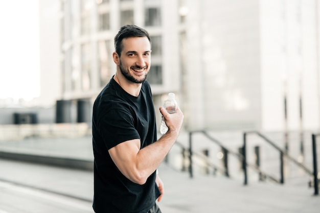 Strong man shows biceps, holds plastic water bottle, looks at camera and smiles. morning city on background. attractive man excercised a lot to get a fit body. hydration time!