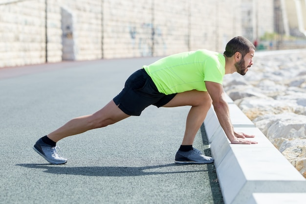 Strong man stretching calf and leaning on curb