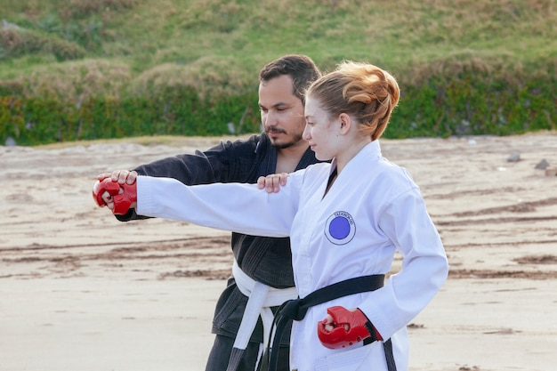 Strong man teaching karate techniques to his female student