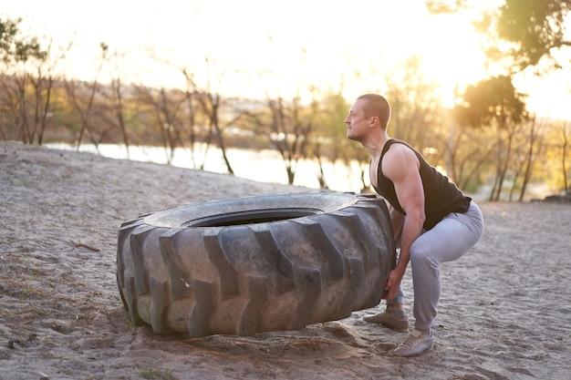 大きなタイヤの屋外diyジムを持ち上げる強い男トレーニングトレーニング。