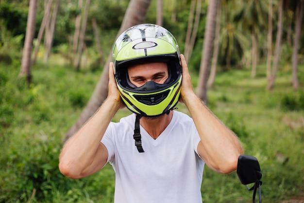 Uomo forte sul campo della giungla tropicale con moto rossa