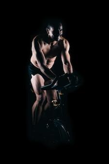 정적 자전거를 사용하는 강한 남자