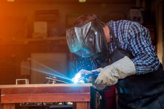作業服を着た強い男の溶接工が一生懸命働き、溶接機の金属で溶接する