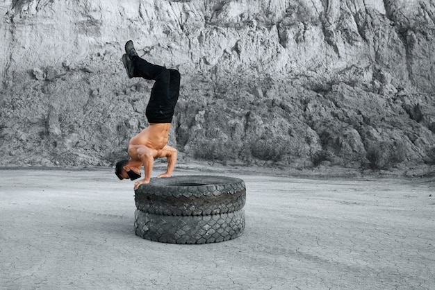 Strong man with bare torso doing push ups on two tyres at sand quarry. active male wearing black face mask and sport pants. concept of outdoors workout.
