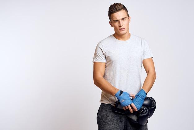 Сильный мужчина в боксерских перчатках и в белой футболке на изолированном