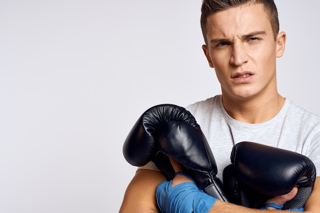 Strong man with boxing gloves and in a white t-shirt on an isolated background cropped view