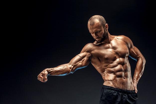 完璧な腹筋、肩、上腕二頭筋、上腕三頭筋、胸を持つ強い男。ボディービルダーは黒い壁の上で彼の筋肉を曲げるトップレス。