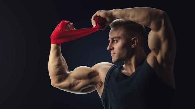 강한 남자가 검은 배경에 손을 감싼다 남자는 검은 배경에 격리된 빨간 권투 랩으로 손을 감싸고 있다 강한 손과 주먹, 훈련 및 활동적인 운동 준비
