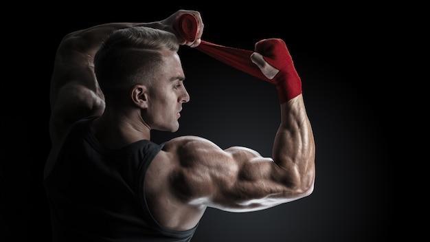 강한 남자가 검은 배경에 손을 감싼다 남자는 검은 배경에 격리된 빨간 권투 랩으로 손을 감싸고 있다