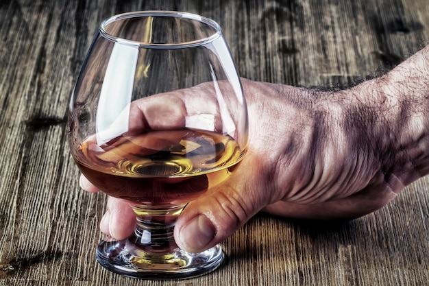 Strong mans hand holding a stylish glass of rum or brandy on rustic old wooden desk.