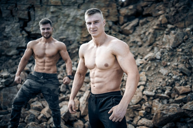 Strong men outdoor. posing to camera. rocky background. male beauty concept.