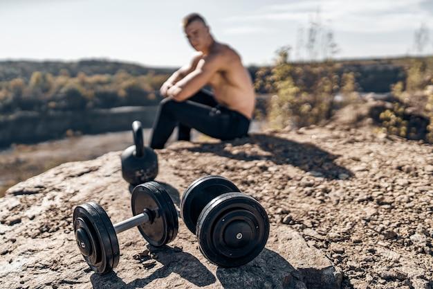 屋外の強い男性。カメラに向かってポーズをとる。岩の背景。男性のスポーツの美しさの概念。岩の上のダンベル。