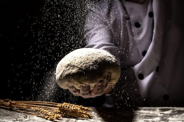 Strong men's hands knead the dough from which they will then make bread, pasta or pizza