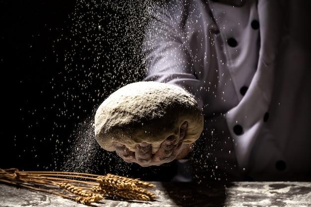 強い男性の手が生地をこねて、パン、パスタ、ピザを作ります