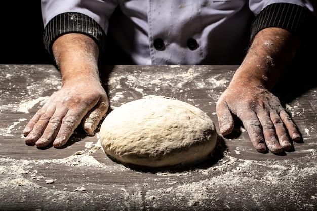 強い男性の手がパン、パスタ、またはピザを作る生地をこねます