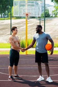 Сильные мужчины пожимают друг другу руки на баскетбольной площадке
