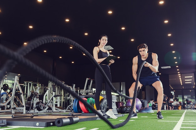 Strong men with battle rope battle ropes exercise in functional fitness gym with female trainer instructor. workout in gym and fitness concept