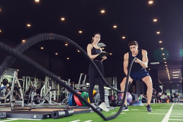 バトルロープを持つ強い男性バトルロープは女性のトレーナーインストラクターと一緒に機能的なフィットネスジムで運動します。ジムとフィットネスの概念でのトレーニング
