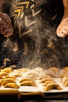 Крепкими мужскими руками посыпать пельмени из муки украинское национальное блюдо