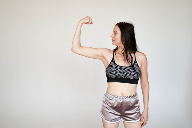 Strong model sporty slim lady wearing sports top and panties showing demonstrating arms muscules on white background with copy space