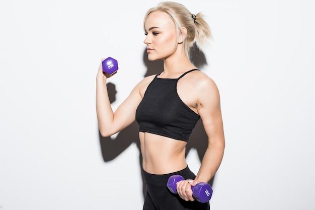 Forte ragazza bionda muscolare che prepara per una competizione con manubri blu su bianco