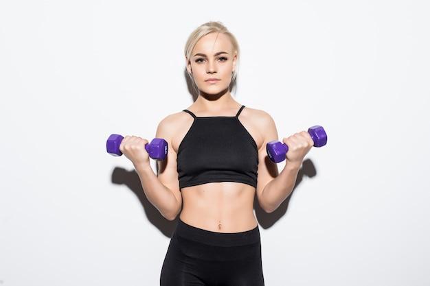 白地に青いダンベルとの競争の準備をして強い筋肉のブロンドの女の子