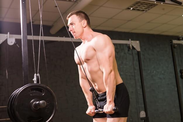 ジムのバーで運動をしている強い筋肉のボディービルダー。フィットネスボディの一部。スポーツとフィットネス。ジムのフィットネスマン。フィットネストレーニング