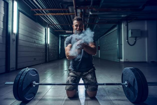 Сильный мускулистый кавказский культурист хлопает в ладоши и приседает в зале. перед ним штанга, все вокруг мелом. подсветка, концепция ночной тренировки.