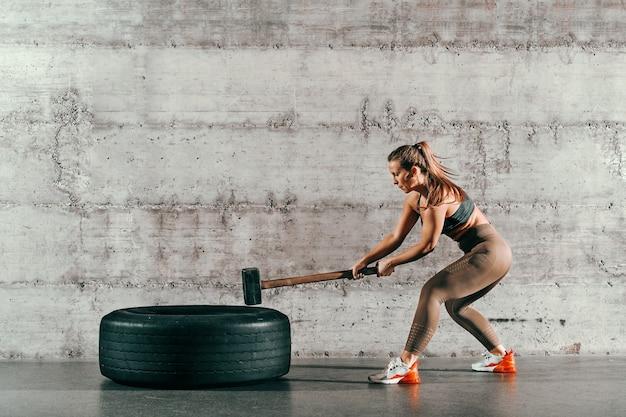 Сильная мускулистая кавказская брюнетка с хвостиком и в спортивной одежде бьет молотком по шине перед серой стеной в тренажерном зале.