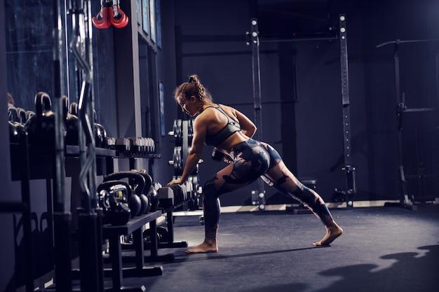 Сильная мышечная кавказская женщина в спортивной одежде и с гантелями подъема косички босиком. резинка салона.
