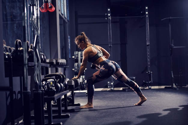 Strong muscular caucasian woman in sportswear and with pigtail lifting dumbbells barefoot. gum interior.