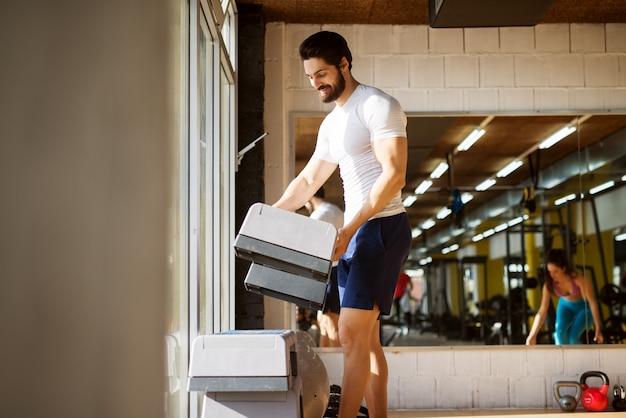 창과 거울 근처 체육관에서 스테퍼를 정렬하는 강한 근육 쾌활한 행복 수염 남자.