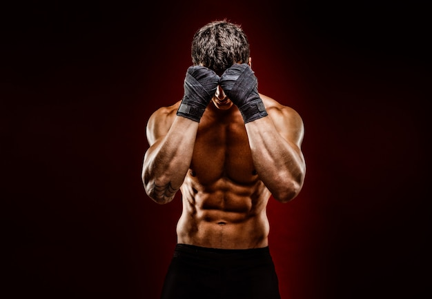 Strong muscular fighter hiding face from camera