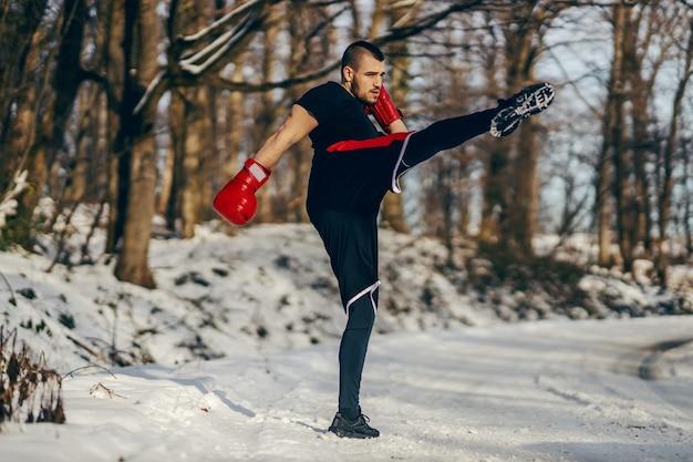 雪の降る冬の日に自然の中でスパーリングボクシンググローブと強力な筋肉の戦闘機