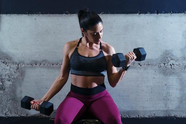 Сильная мускулистая фитнес-женщина, усердно работающая в тренажерном зале, поднимая тяжести и тренируя бицепсы