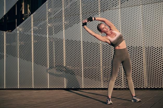 운동복에 강한 근육질 소녀는 벽 앞에서 운동 후 스트레칭 운동을하고 있습니다.