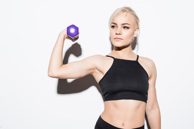 Forte ragazza muscolare che prepara per una competizione con manubri blu su bianco