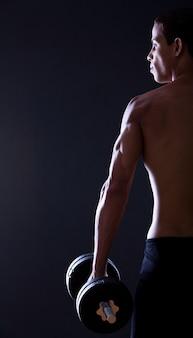 Ragazzo forte e muscoloso con manubri
