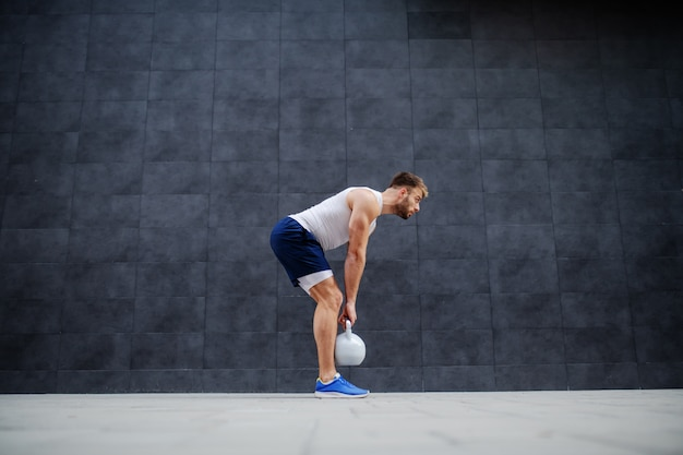 Strong muscular handsome caucasian man in shorts and t-shirt standing outdoors and lifting kettle bell. in background is gray wall.