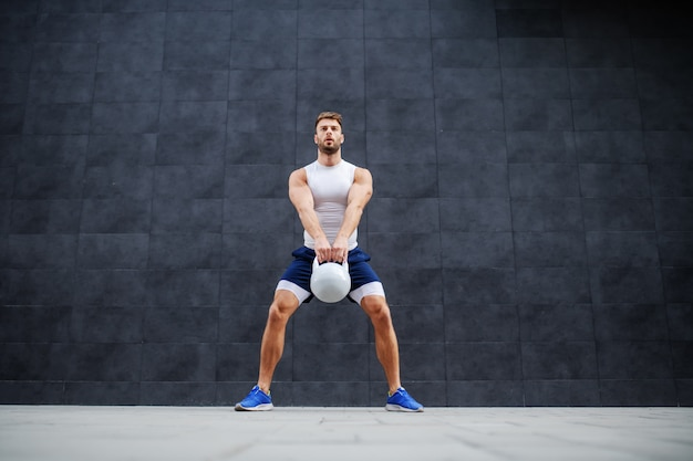 Strong muscular handsome caucasian man in shorts and t-shirt standing outdoors and swinging kettle bell. in background is gray wall.