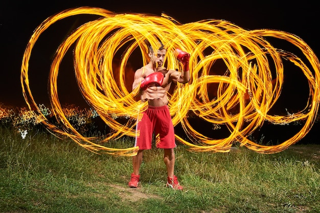 Strong muscular male fighter posing with fire and flames