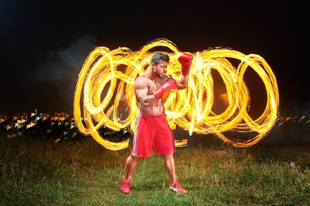 Strong muscular male fighter with fire and flames behind his bac