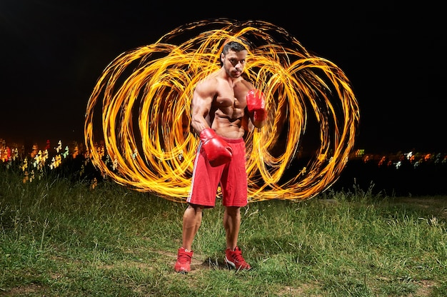Strong muscular male fighter with fire and flames behind
