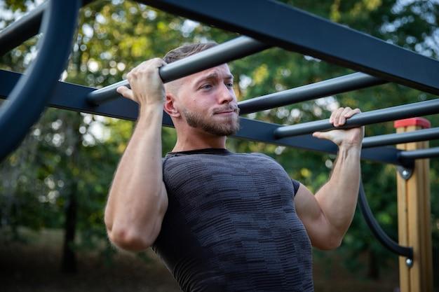 Сильный мускулистый мужчина делает несколько подтягиваний во время тренировки на свежем воздухе в парке и выражает усилие гримаса