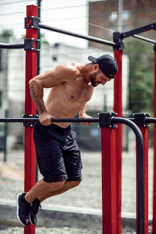 Strong muscular man doing push-ups on uneven bars in outdoor street gym