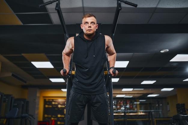 Сильный мускулистый мужчина делает отжимания на брусьях в концепции образа жизни тренировки в тренажерном зале