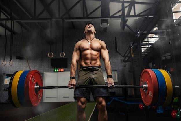 強い筋肉質の男が重いバーベルを持って叫び、暗い雰囲気のジムでデッドリフトを行う。