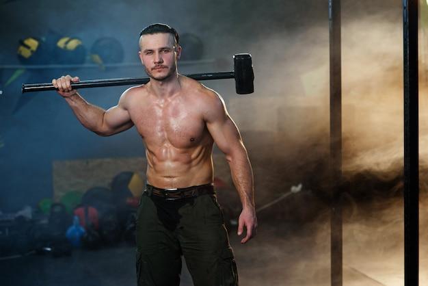Сильный мускулистый мужчина с молотком на плече.
